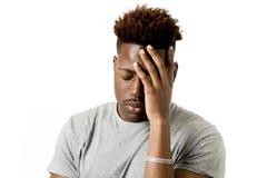 Jonge aantrekkelijke afro Amerikaanse mens die op zijn jaren '20 het droevige en gedeprimeerde emotioneel stellen kijken Stock Fotografie