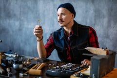 Jonge aantrekkelijke artisanaal controlerend de kwaliteit van amber in de juwelenwinkel stock foto's