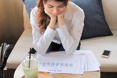 Jonge aantrekkelijke Aziatische bedrijfsvrouw die grafieken of documentdossiers in haar bureau analyseren Selectieve nadruk en on Stock Fotografie