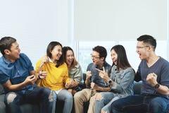 Jonge Aantrekkelijke Aziatische groep vrienden die en met gelukkig in thuis het verzamelen van vergaderingszitting spreken lachen royalty-vrije stock foto's