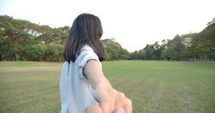 Jonge aantrekkelijke Aziatische vrouw die haar vriend trekken door een de zomerpark bij zonsondergang stock video