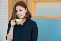 Jonge aantrekkelijke Aziatische vrouw die van haar heerlijke hete koffie i genieten royalty-vrije stock afbeelding