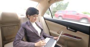 Jonge aantrekkelijke Aziatische vrouwenzitting op de achterbank in taxi en het gebruiken van haar laptop stock videobeelden