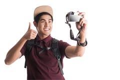 Jonge aantrekkelijke backpacker die een selfie met een camera nemen isolat royalty-vrije stock foto