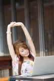 Jonge aantrekkelijke bedrijfsdievrouw die en zich op haar lapt wordt vermoeid uitrekken Royalty-vrije Stock Fotografie
