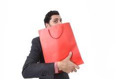 Jonge aantrekkelijke bedrijfsmens die in spanningsholding het winkelen zak gulzig na het kopen koopje kijken Stock Afbeeldingen
