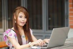 Jonge aantrekkelijke bedrijfsvrouw die aan haar laptop bij openlucht werken Royalty-vrije Stock Foto