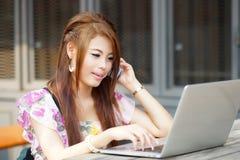 Jonge aantrekkelijke bedrijfsvrouw die aan haar laptop bij openlucht werken Royalty-vrije Stock Afbeeldingen