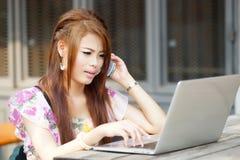 Jonge aantrekkelijke bedrijfsvrouw die aan haar laptop bij openlucht werken Stock Foto