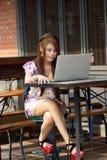 Jonge aantrekkelijke bedrijfsvrouw die aan haar laptop bij openlucht werken Stock Afbeeldingen