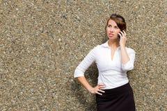 Jonge aantrekkelijke bedrijfsvrouwenstafmedewerker die haar slimme telefoon met behulp van Royalty-vrije Stock Fotografie