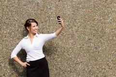 Jonge aantrekkelijke bedrijfsvrouwenstafmedewerker die haar slimme telefoon met behulp van Stock Fotografie