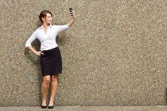 Jonge aantrekkelijke bedrijfsvrouwenstafmedewerker die haar slimme telefoon met behulp van Royalty-vrije Stock Foto