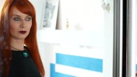 Jonge aantrekkelijke blije Kaukasische vrouw die zwarte kleding dragen die spiegel onderzoeken, die klaar worden stock footage