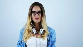 Jonge aantrekkelijke blonde glimlachende vrouw in oogglazen kauwgom met hoofdtelefoons op haar hals op geïsoleerde witte achtergr stock footage