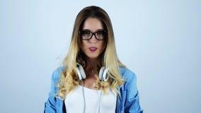 Jonge aantrekkelijke blondevrouw die in oogglazen kauwgom met hoofdtelefoons op haar hals op geïsoleerde witte achtergrond opblaz stock footage