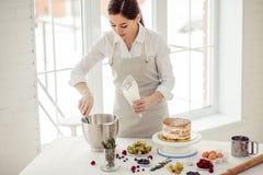 Jonge aantrekkelijke chef-kok die room in de gebakjezak zetten stock afbeelding
