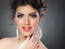Jonge aantrekkelijke donkerbruine dame met creatieve make-up en het mooie kapsel stellen op grijze achtergrond in studio Dicht Po Stock Fotografie