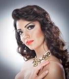 Jonge aantrekkelijke donkerbruine dame met make-up en het mooie kapsel stellen op grijze achtergrond in studio Stock Afbeeldingen