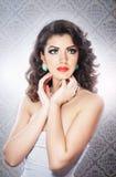 Jonge aantrekkelijke donkerbruine dame met make-up en het mooie kapsel stellen op grijze achtergrond in studio Royalty-vrije Stock Foto's