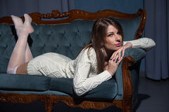 Jonge aantrekkelijke donkerbruine vrouw die op een bank liggen Royalty-vrije Stock Foto's