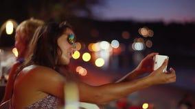 Jonge aantrekkelijke donkerbruine vrouw in zonnebril die makend gezichten die selfie foto nemen die smartphone met flits gebruike stock videobeelden