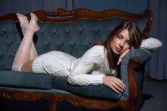 Jonge aantrekkelijke donkerbruine vrouwenslaap op een bank Stock Fotografie