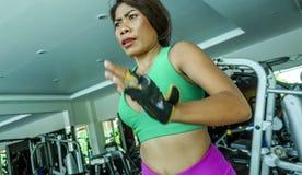 Jonge aantrekkelijke en atletische Aziatische Indonesische sportvrouw die op tredmolen bij gymnastiekfitness club lopen die harde stock foto's