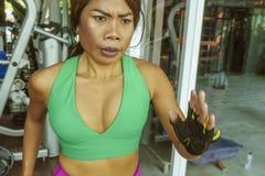 Jonge aantrekkelijke en atletische Aziatische Indonesische sportvrouw die op tredmolen bij gymnastiekfitness club lopen die harde stock foto
