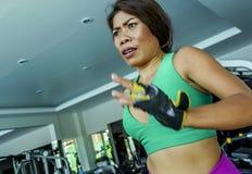 Jonge aantrekkelijke en atletische Aziatische Indonesische sportvrouw die op tredmolen bij gymnastiekfitness club lopen die harde stock afbeeldingen