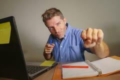 Jonge aantrekkelijke en gelukkige bedrijfsmens die met laptop computer thuis bureau werken die het tevreden en zekere richten gli Stock Afbeeldingen