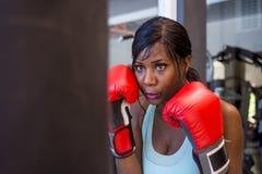 Jonge aantrekkelijke en mooie bepaalde zwarte afro Amerikaanse vrouw in gymnastiek opleiding zwetend op zwaar zakponsen met boksh royalty-vrije stock foto