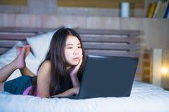 Jonge aantrekkelijke en mooie jaren '20 Aziatische Chinese vrouw die op bed bij nacht die Internet gebruiken die in laptop comput Royalty-vrije Stock Foto's