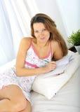 Jonge aantrekkelijke en mooie vrouw in nachtjapon ontspannen liggen Stock Afbeelding