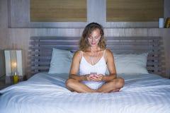 Jonge aantrekkelijke en mooie vrouw thuis in bed die de sociale media app van Internet bij het mobiele telefoon gelukkig glimlach royalty-vrije stock fotografie