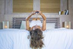 Jonge aantrekkelijke en mooie vrouw thuis in bed die de sociale media app van Internet bij het mobiele telefoon gelukkig glimlach stock foto's