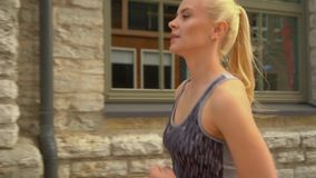 Jonge, aantrekkelijke en sportieve blonde meisjesjogging openlucht in de straten Gezondheidszorg, sport, fitness en levensstijl stock footage