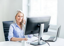 Jonge, aantrekkelijke en zekere bedrijfsvrouw die in bureau werken Royalty-vrije Stock Foto