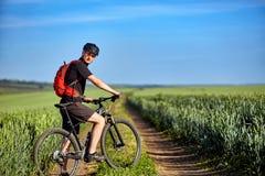 Jonge aantrekkelijke fietser die met bergfietser opstaan op het de zomer groene gebied Stock Fotografie