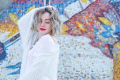 Jonge aantrekkelijke freckled vrouw die met rode lippen in witte vrijetijdskleding het stellen in de straat lopen royalty-vrije stock foto