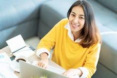 Jonge aantrekkelijke gelukkige Aziatische vrouwelijke studentenzitting bij woonkamervloer die en omhoog camera glimlachen bekijke royalty-vrije stock afbeelding