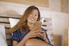 Jonge aantrekkelijke gelukkige en ontspannen Aziatische tienervrouw in pyjama's thuis bed het gebruiken daterend app of texting h stock afbeeldingen