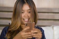 Jonge aantrekkelijke gelukkige en ontspannen Aziatische tienervrouw in pyjama's thuis bed het gebruiken daterend app of texting h stock foto