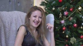Jonge aantrekkelijke gelukkige vrouw die en op de achtergrond van de Kerstmisboom lachen zitten stock video