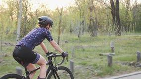 Jonge aantrekkelijke geschikte vrouw die een fiets in het park berijden Opleiding voor een ras Het cirkelen concept Langzame Moti stock videobeelden