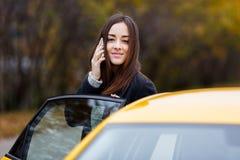 Jonge aantrekkelijke glimlachende vrouw die op mobiele telefoon dichtbij taxi spreken Stock Foto