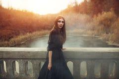 Jonge aantrekkelijke Heks die op de brug in zware zwarte rook lopen stock afbeeldingen