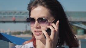 Jonge Aantrekkelijke Kaukasische Vrouw in Zonnebril die Pret hebben die op Telefoon spreken stock footage