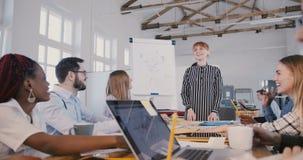 Jonge aantrekkelijke Kaukasische vrouwelijke bedrijfwerkgever die een motivatietoespraak geven, die met multi-etnisch team bij ve stock footage