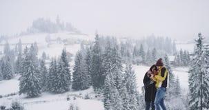 Jonge aantrekkelijke kerel en dame die zich op de bovenkant die van gebiedsachtergrond bevinden sneeuwbos verbazen, zij die bekij stock video